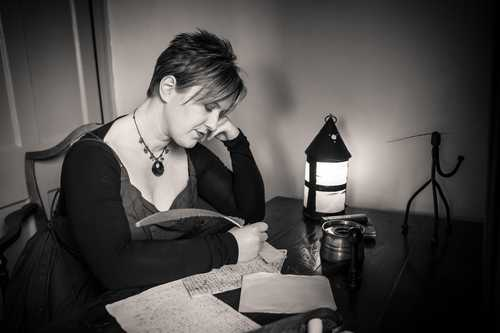 A photo of Ange Hardy working at Samuel Taylor Coleridge's writing desk